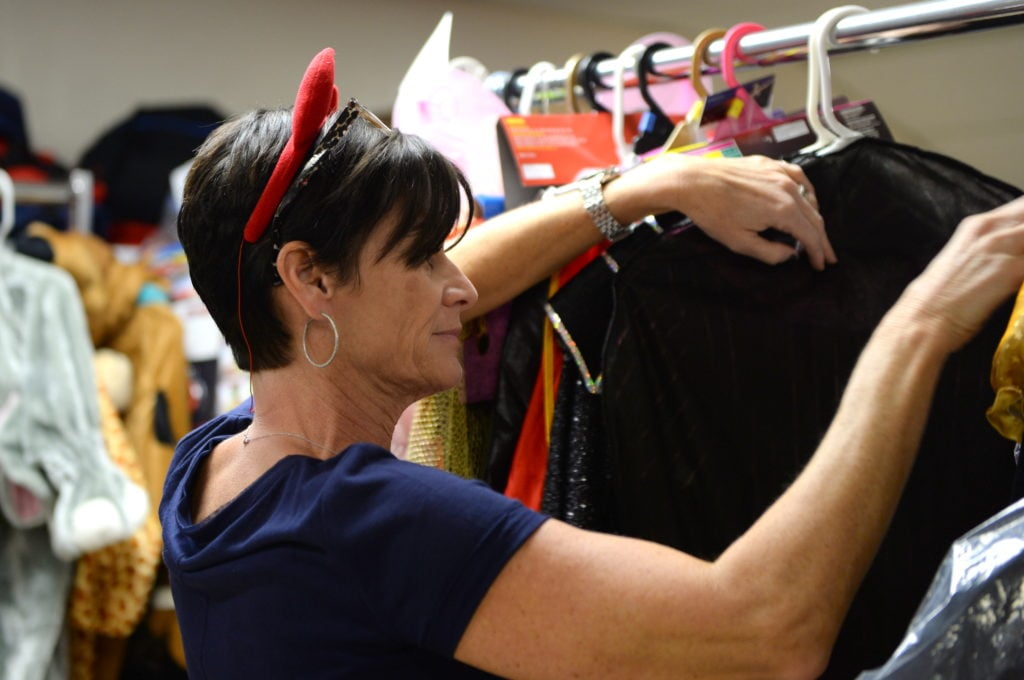 Judy sorts through costumes on distribution day, looking for the perfect match. Photo by Hurley Event Photography.