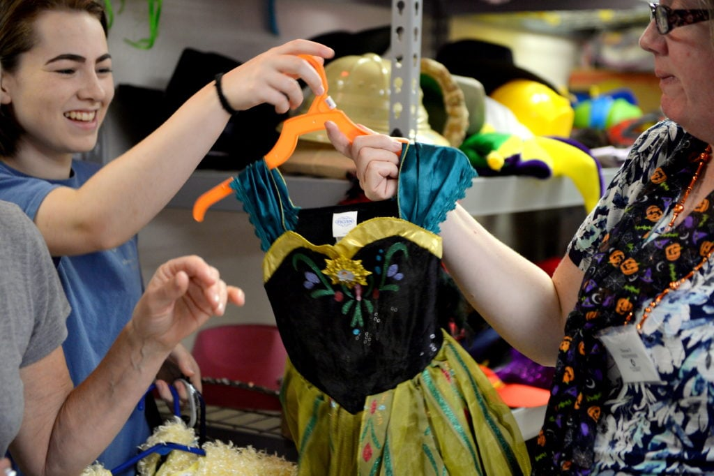 Therese hands volunteer Lily a Frozen costume for a client. Photo by Hurley Event Photography.