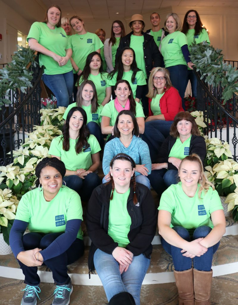 Arbella volunteers (in green shirts) and Paula Daniels, Interfaith's Development Director, on the morning of the event.