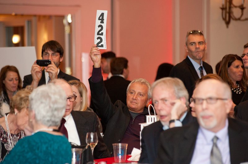 Guest John Tallarida holds up his paddle during the auction.