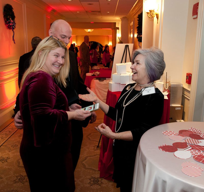 Food pantry manager Eileen Kelly, right, chats with guests at the Giving Tree, a station where guests could purchase an ornament which in turn provides holiday gifts for children of Interfaith's food pantry clients.