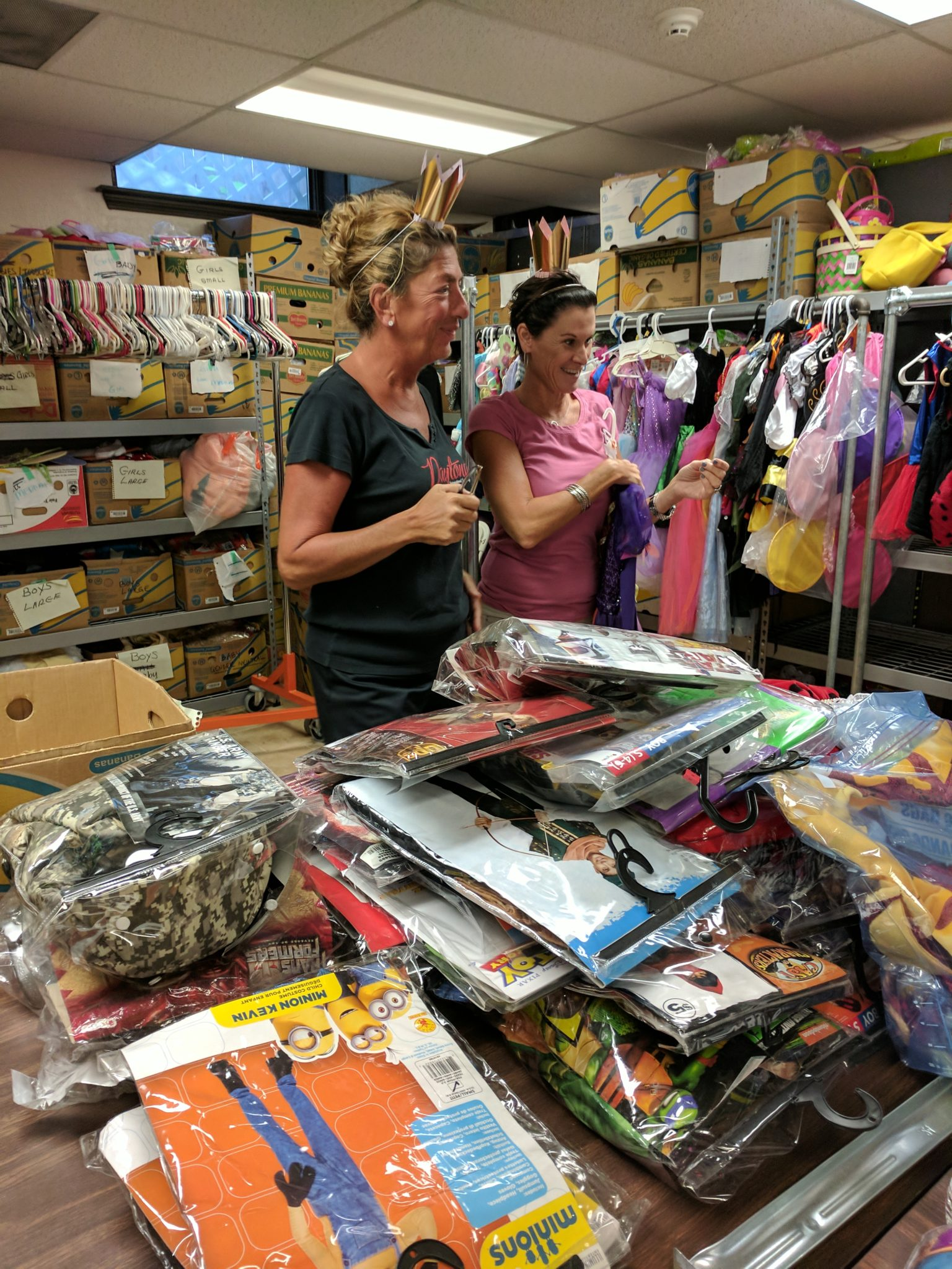 Robin and Judy sort through mounds of costume donations in the weeks leading up to distribution day. Photo by Jennifer Sammons.