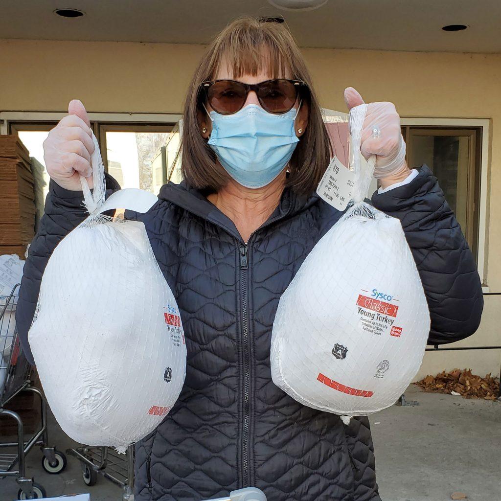 Volunteer holding two donated turkeys