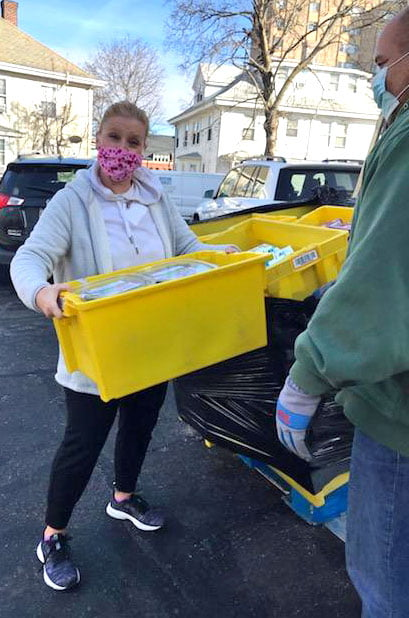 Volunteer Jennifer lifts a yellow bin of food on her volunteer shift