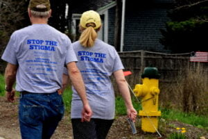 """backs of two people walking while wearing """"Stop the Stigma"""" shirts"""