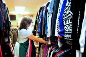 Volunteer hanging clothing on racks in Interfaith's Bureau Drawer Thrift Shop