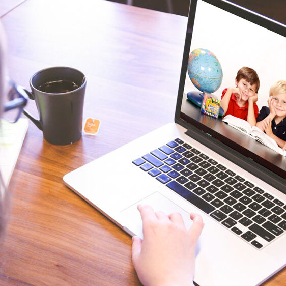 teacher with mug of tea typing on laptop showing image of two young students