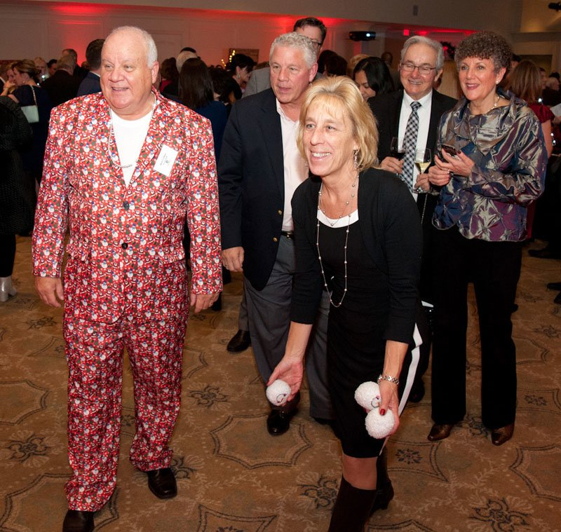 Ron Collins (snowman suit), an Interfaith volunteer , watches as guest Barbara Pyne tries out the Snowball Toss game.